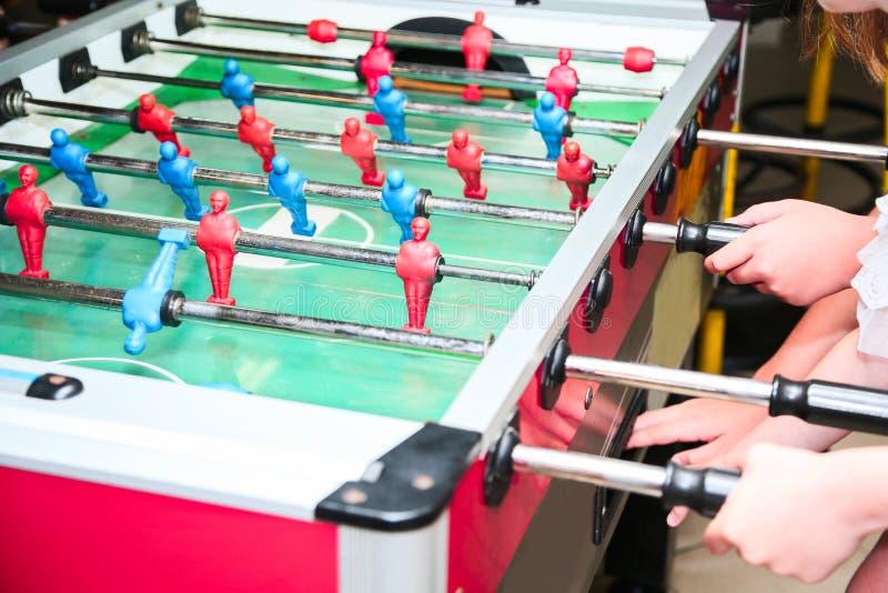 孩子的手细节参加foosball桌比赛的 足球,朋友休闲 图库摄影