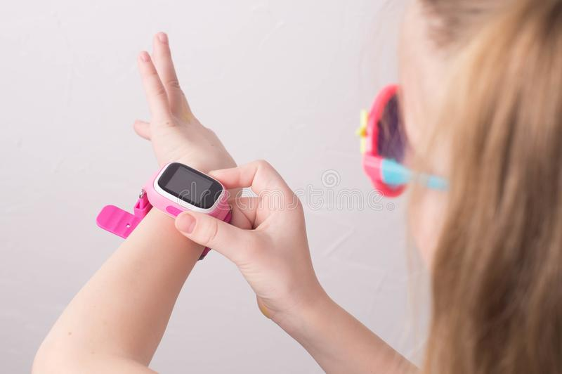 孩子的技术:戴桃红色眼镜的女孩使用一smartwatch 免版税库存图片