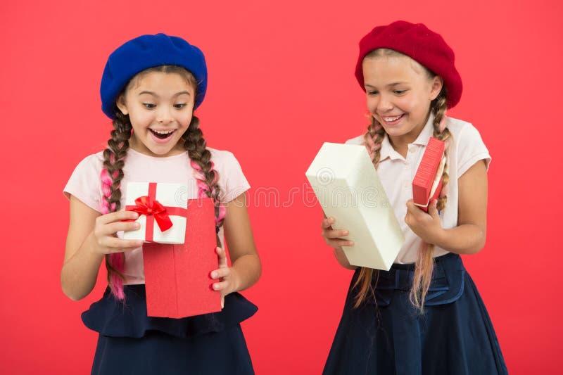 孩子的最佳的礼物 校服和贝雷帽举行礼物盒的孩子女孩 孩子被激发关于打开 库存图片