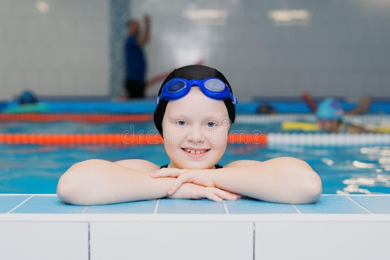 孩子的水池的-一个美丽的白被剥皮的女孩的画象游泳教训一个游泳衣和游泳盖帽的 库存图片