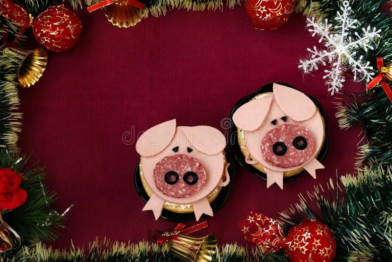 孩子的滑稽的三明治塑造了逗人喜爱的猪用乳酪和香肠 免版税库存图片