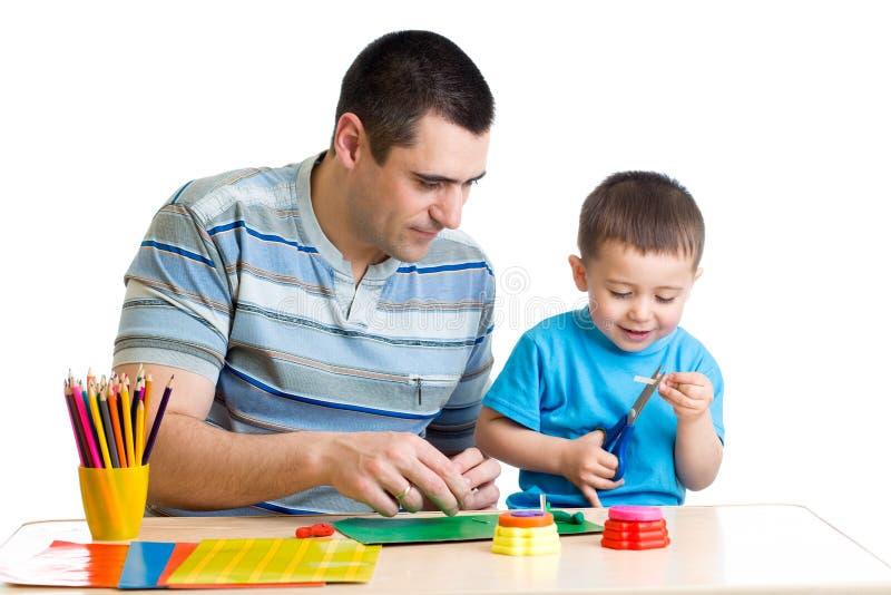 孩子的男孩和一起使用他的爸爸 免版税图库摄影