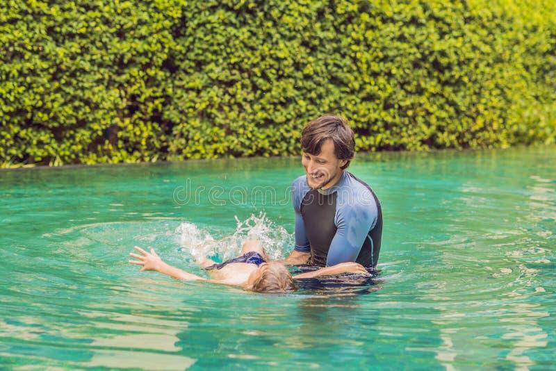 孩子的男性辅导员游泳在水池教一个愉快的男孩游泳 免版税库存图片