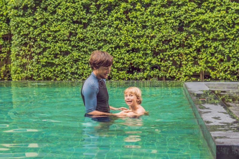 孩子的男性辅导员游泳在水池教一个愉快的男孩游泳 免版税库存照片
