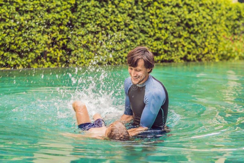 孩子的男性辅导员游泳在水池教一个愉快的男孩游泳 图库摄影