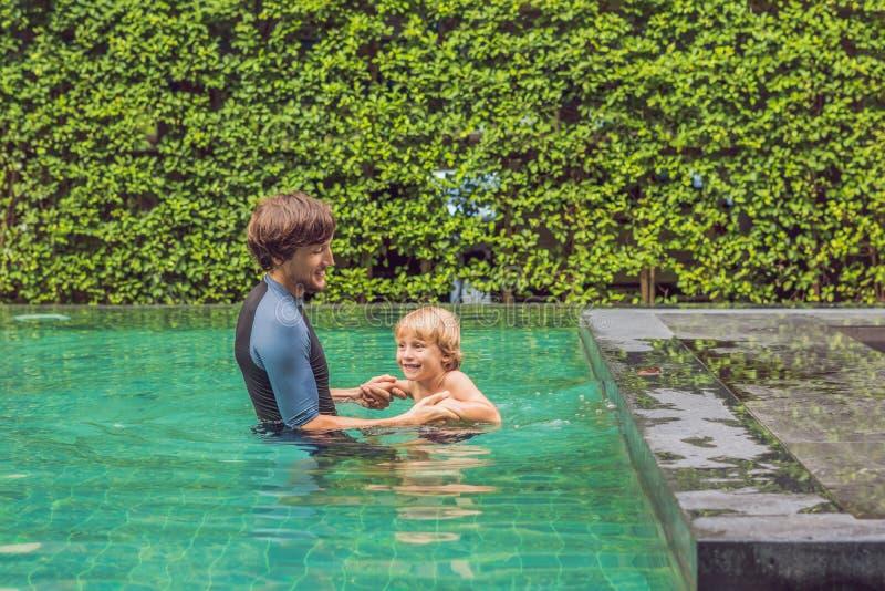 孩子的男性辅导员游泳在水池教一个愉快的男孩游泳 库存图片