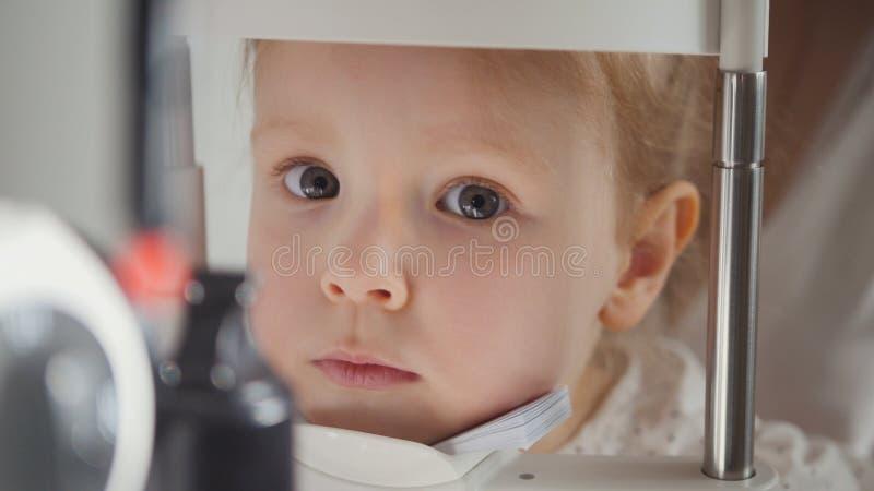 孩子的眼科学诊所-验光师诊断小白肤金发的女孩 免版税库存图片