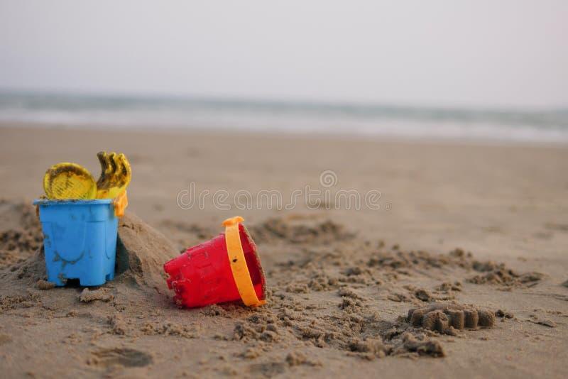 孩子的红色和蓝色玩具桶在沙子海滩 免版税库存图片