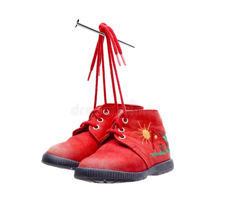 孩子的老红色鞋子被栓对钉子 库存图片