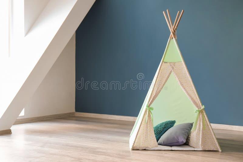 孩子的舒适戏剧帐篷在颜色墙壁附近 免版税库存照片