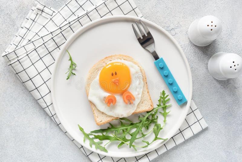 孩子的逗人喜爱的滑稽的早餐 鸡塑造了三明治或多士在白色板材 免版税库存照片