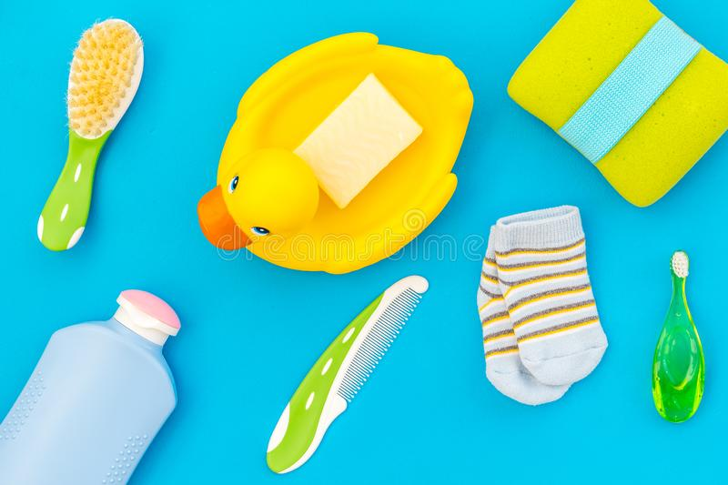 孩子的阵雨辅助部件 设置与香波、毛巾、肥皂、胶凝体、刷子和黄色橡胶鸭子在蓝色背景上面 免版税图库摄影