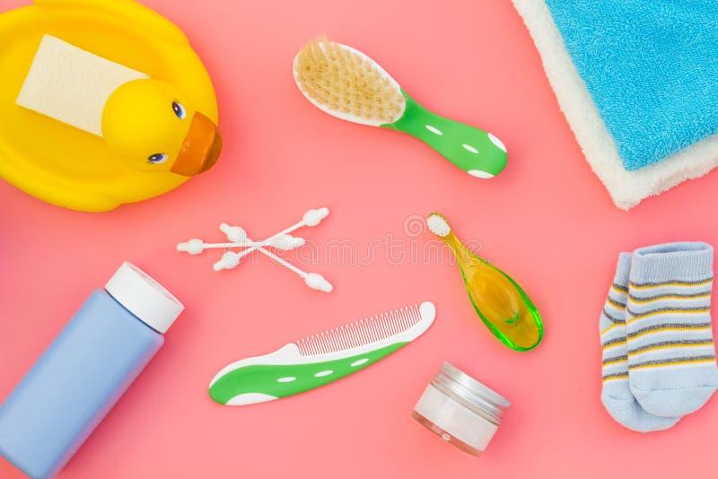 孩子的阵雨辅助部件 设置与香波、毛巾、肥皂、胶凝体、毛巾、刷子和黄色橡胶鸭子在桃红色背景 免版税库存图片
