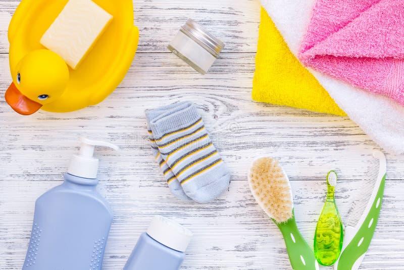 孩子的阵雨辅助部件 设置与香波、毛巾、肥皂、胶凝体、毛巾、刷子和黄色橡胶鸭子在灰色木 库存照片