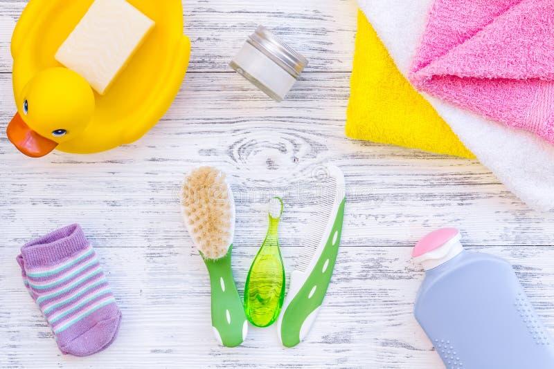 孩子的阵雨辅助部件 设置与香波、毛巾、肥皂、胶凝体、毛巾、刷子和黄色橡胶鸭子在灰色木 免版税库存照片