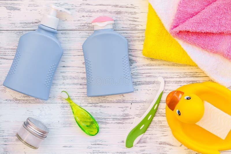 孩子的阵雨辅助部件 设置与香波、毛巾、肥皂、胶凝体、毛巾、刷子和黄色橡胶鸭子在灰色木 免版税库存图片