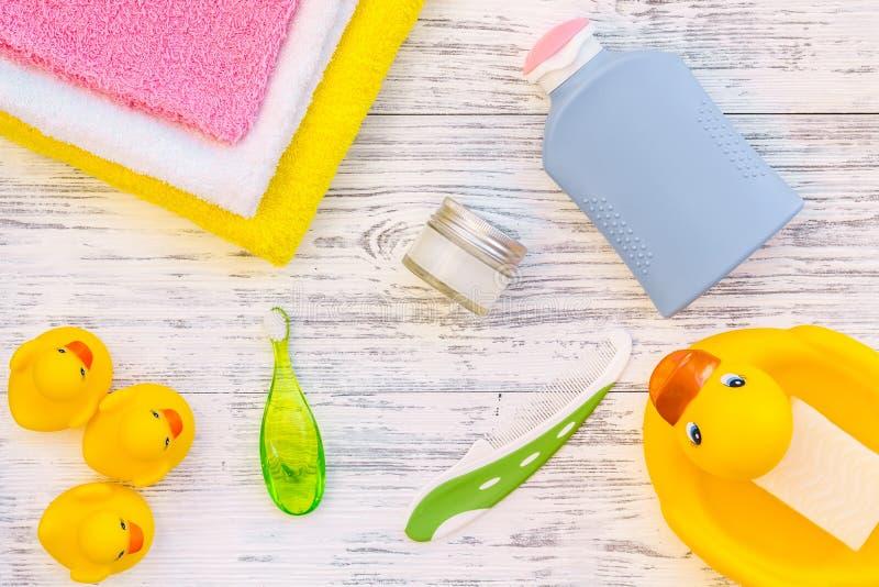 孩子的阵雨辅助部件 设置与香波、毛巾、肥皂、胶凝体、毛巾、刷子和黄色橡胶鸭子在灰色木 库存图片