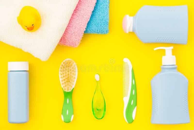 孩子的阵雨辅助部件 设置与香波、毛巾、肥皂、胶凝体、毛巾、刷子和黄色橡胶鸭子在黄色 免版税库存图片