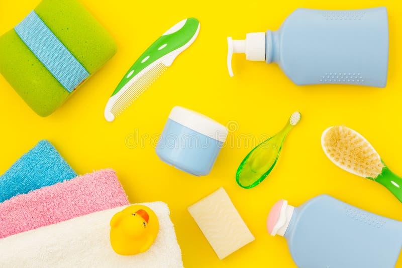 孩子的阵雨辅助部件 设置与香波、毛巾、肥皂、胶凝体、毛巾、刷子和黄色橡胶鸭子在黄色 库存图片