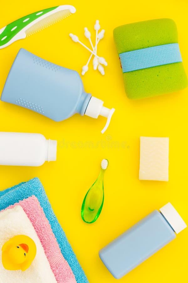 孩子的阵雨辅助部件 设置与香波、毛巾、肥皂、胶凝体、毛巾、刷子和黄色橡胶鸭子在黄色 库存照片