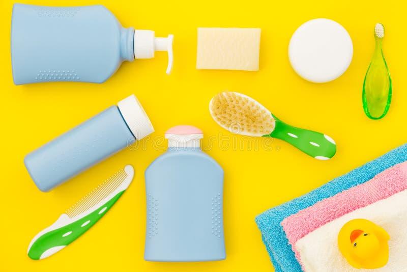 孩子的阵雨辅助部件 设置与香波、毛巾、肥皂、胶凝体、毛巾、刷子和黄色橡胶鸭子在黄色 图库摄影