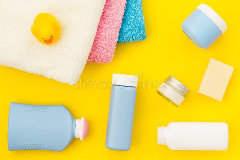 孩子的阵雨辅助部件 设置与香波、毛巾、肥皂、胶凝体、毛巾、刷子和黄色橡胶鸭子在黄色 免版税库存照片