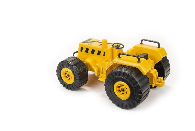 孩子的黄色拖拉机玩具白色背景的 图库摄影