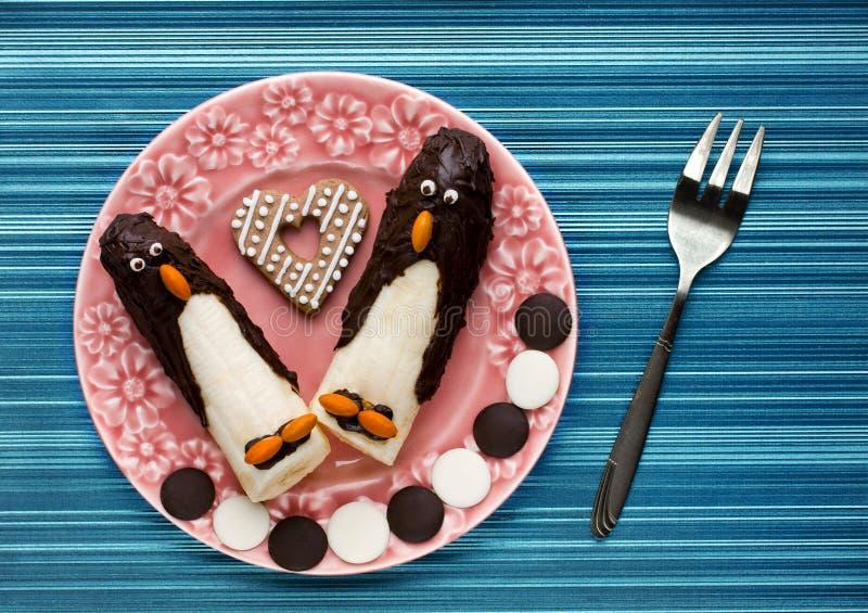 孩子的滑稽的早餐:在巧克力形状的pengui的香蕉 库存图片