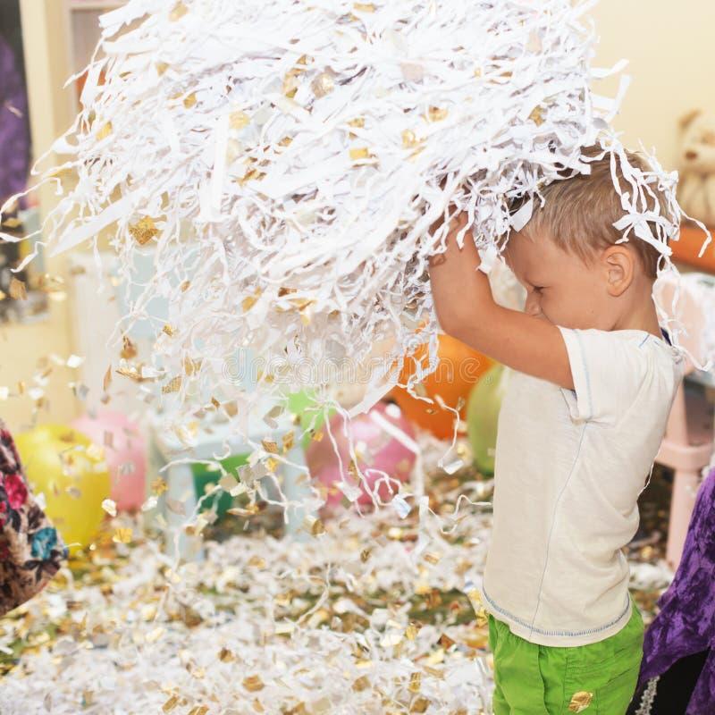 孩子的画象投掷多彩多姿的闪亮金属片和纸骗局 图库摄影