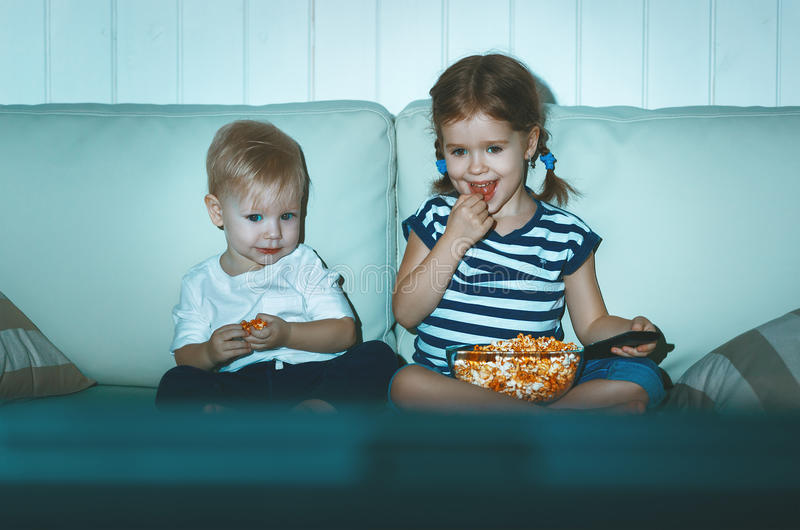孩子看电视的兄弟和姐妹在晚上 库存图片