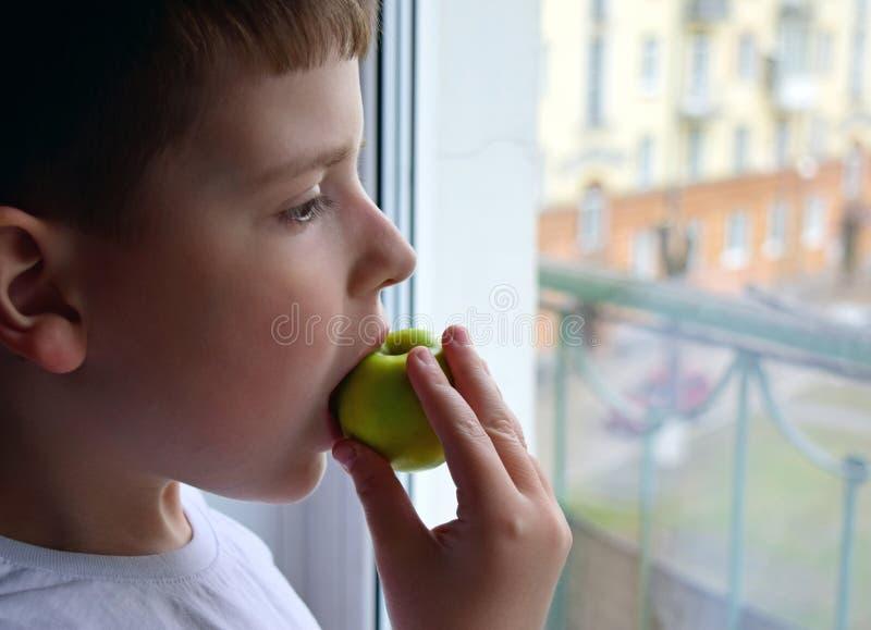 孩子看窗口并且咬住绿色苹果 男孩在他的手上拿着一个苹果 免版税库存照片