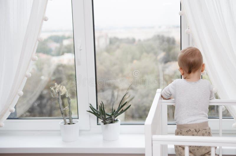 孩子看窗口 图库摄影