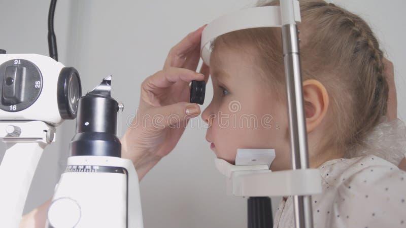 孩子眼科学-检查小孩` s视觉的验光师 免版税库存图片
