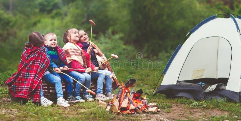 孩子笑并且油煎香肠在利益靠近帐篷 库存照片