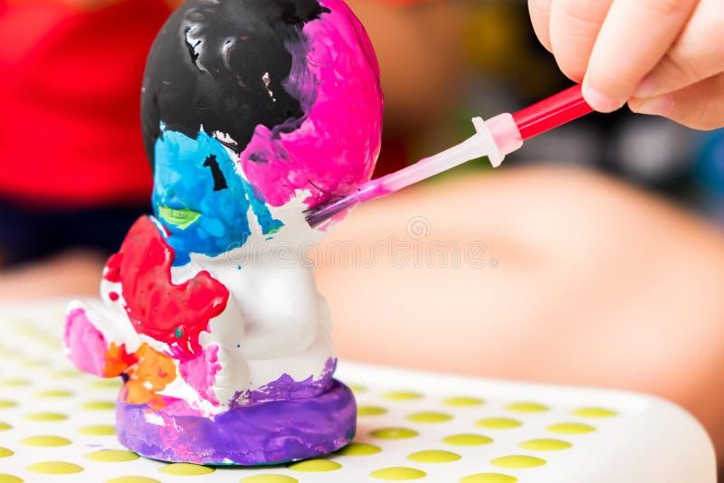 孩子绘与五颜六色的颜色的雕塑 它` s乐趣滚刀 库存照片