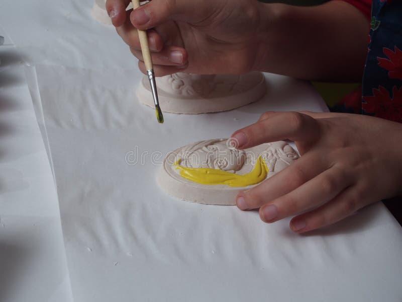 孩子绘与油漆的膏药浅浮雕 库存照片
