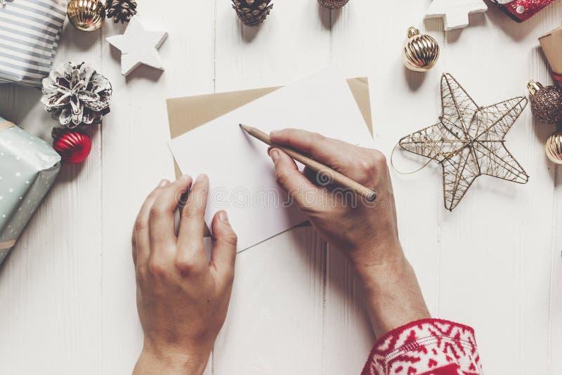 孩子给圣诞老人顶视图写信 举行p的孩子手 免版税库存图片