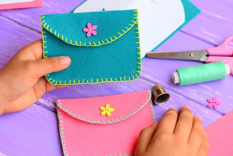 孩子缝合了一个钱包毛毡 小孩子在他的手上拿着一个明亮的毛毡钱包 工艺供应,毛毡diy在一张木桌上 库存照片