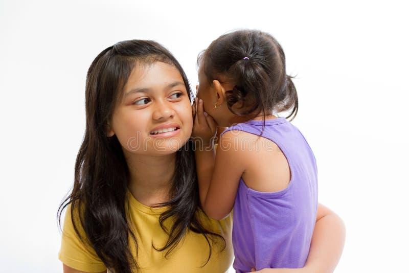 孩子耳语秘密故事对更老的姐妹 库存图片