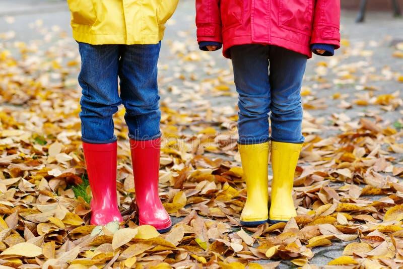 孩子腿特写镜头在跳舞和走通过秋天叶子的胶靴的 免版税库存图片