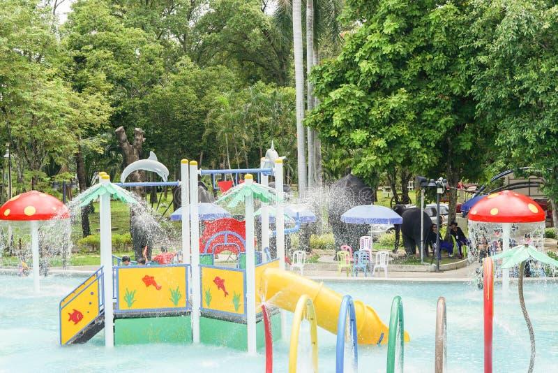 孩子获得乐趣在五颜六色的操场在水公园 免版税库存照片