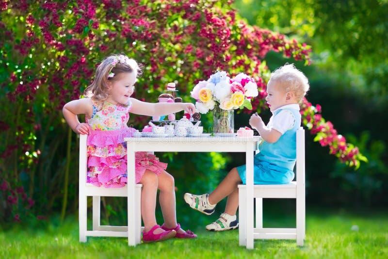 孩子获得乐趣在庭院茶会 免版税库存照片