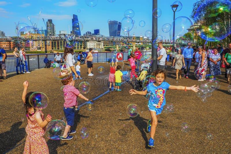 孩子获得使用与在泰晤士bankside的五颜六色的肥皂泡的很多乐趣在千年桥梁附近在伦敦 库存图片