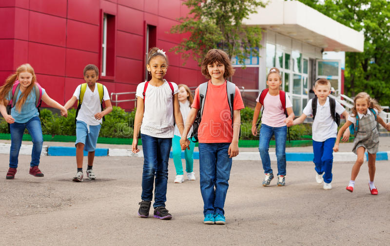 孩子行与背包的临近学校走 免版税图库摄影