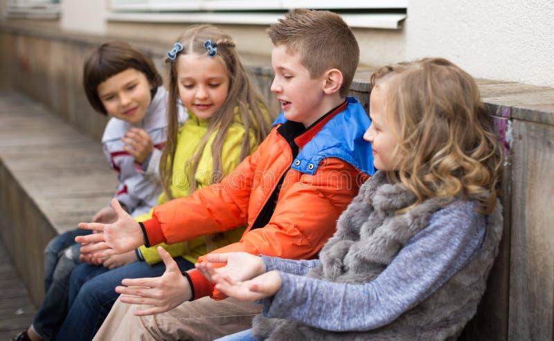 孩子谈话在长凳 免版税库存照片