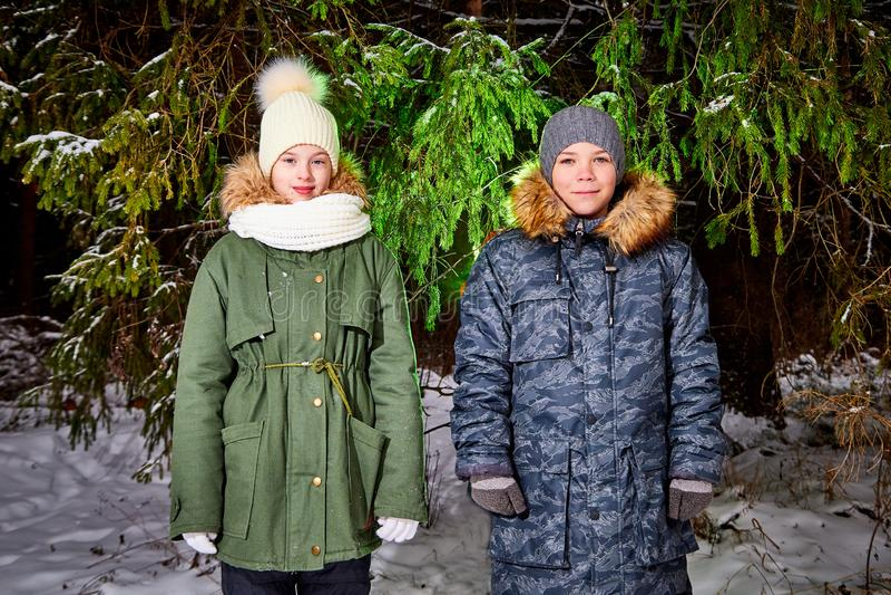 孩子走在雪森林里的男孩和女孩在一个冬日 少年有旅行和休息在室外的周末 库存图片
