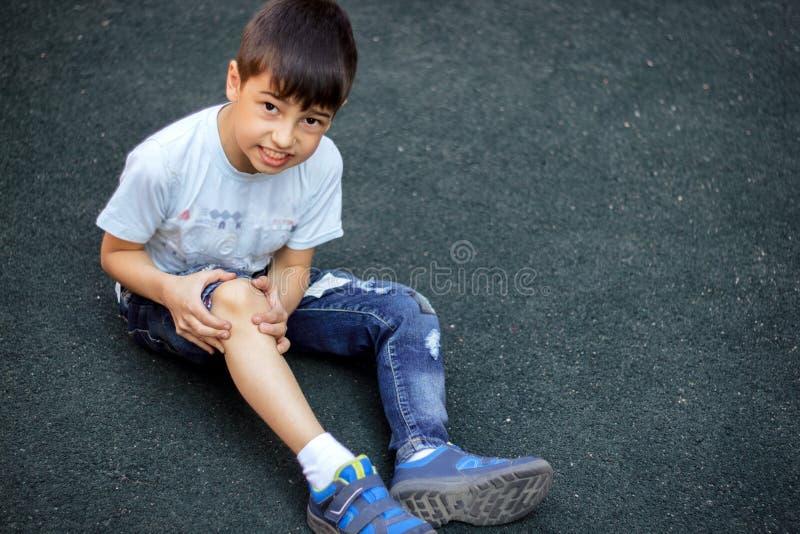 孩子跌倒了并且击中了他的膝盖,男孩在边路绊倒了并且跌倒了 库存照片