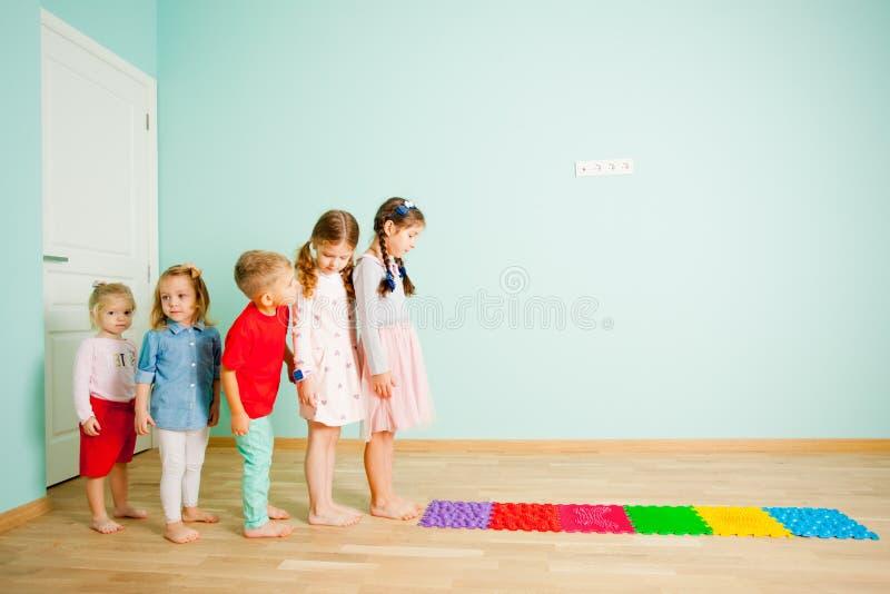 孩子连续赤足站立在按摩席子之间 免版税库存照片