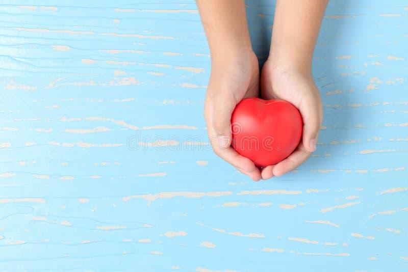 孩子递拿着在蓝色木头的红色心脏 库存照片