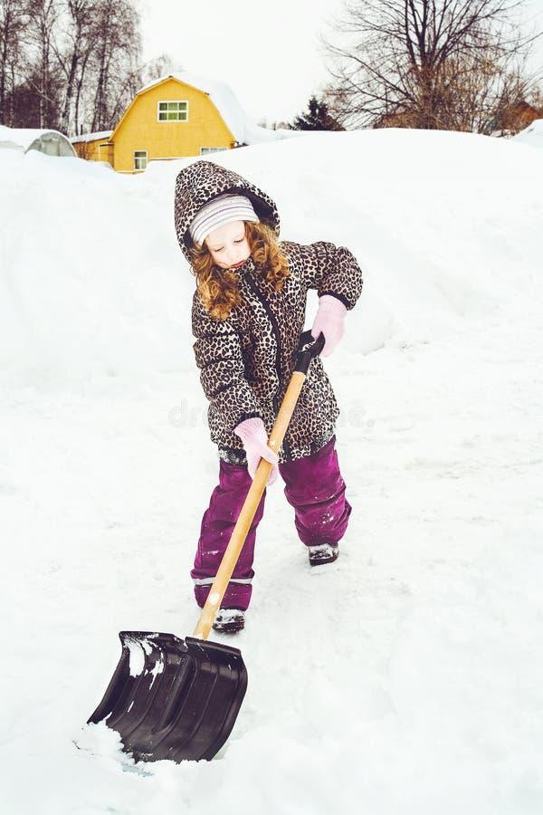 孩子铲起在他的房子前面的雪 免版税库存图片